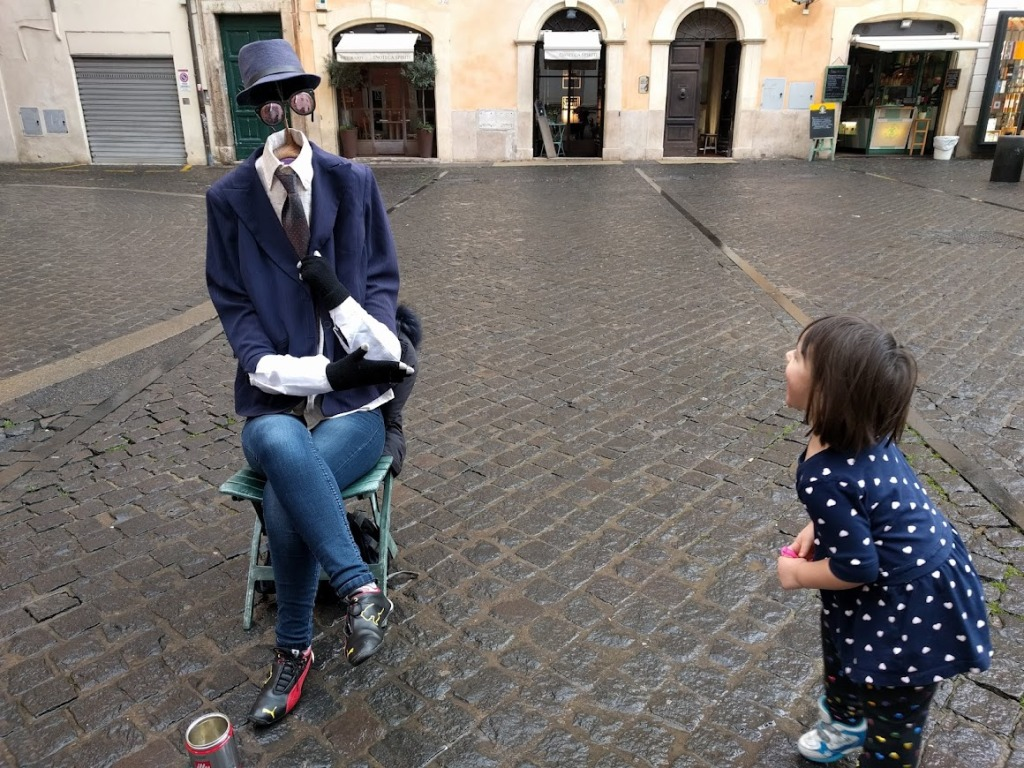 A young child laughing at a street performer who is posing as an invisible man.